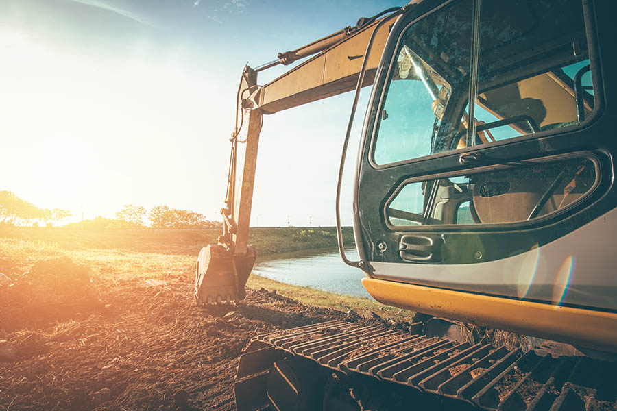 Excavation Contractor Insurance - Truck Digging into the Earth for a Building Project
