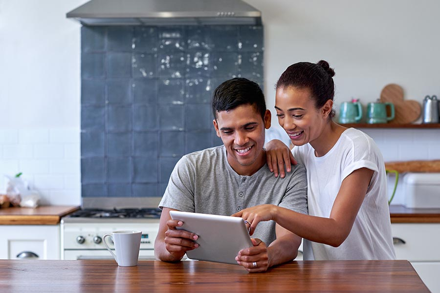 Blog - Couple Smiles as They Use a Tablet in Their High-End Kitchen, Coffee Nearby