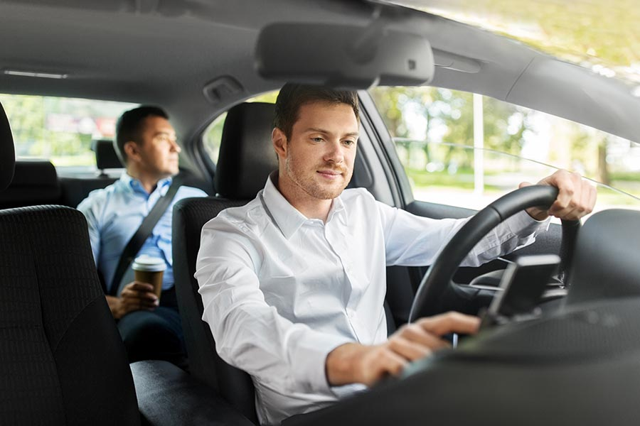 Rideshare Insurance - Professional Ride Share Driver Checks in on His Phone, a Client in the Back Seat