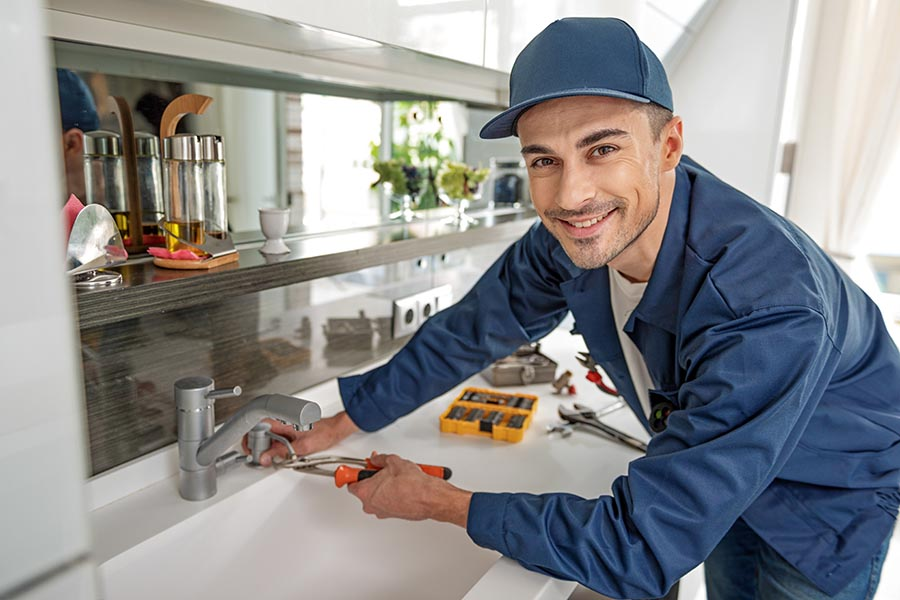 Specialized Business Insurance - Contractor Works on a Faucet Installation in a Home Wearing Blue Uniform